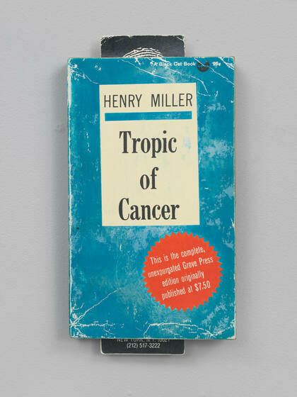 """The front cover of a blue book titled """"Tropic of Cancer"""" with frayed corners and creased sections"""