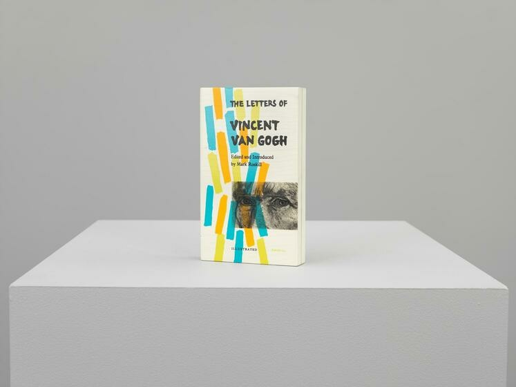 """A lifelike sculpture of a book titled """"Van Gogh letters"""", feautring a image of Van Gogh's eyes and rectangular blocks of blue, yellow, and orange"""