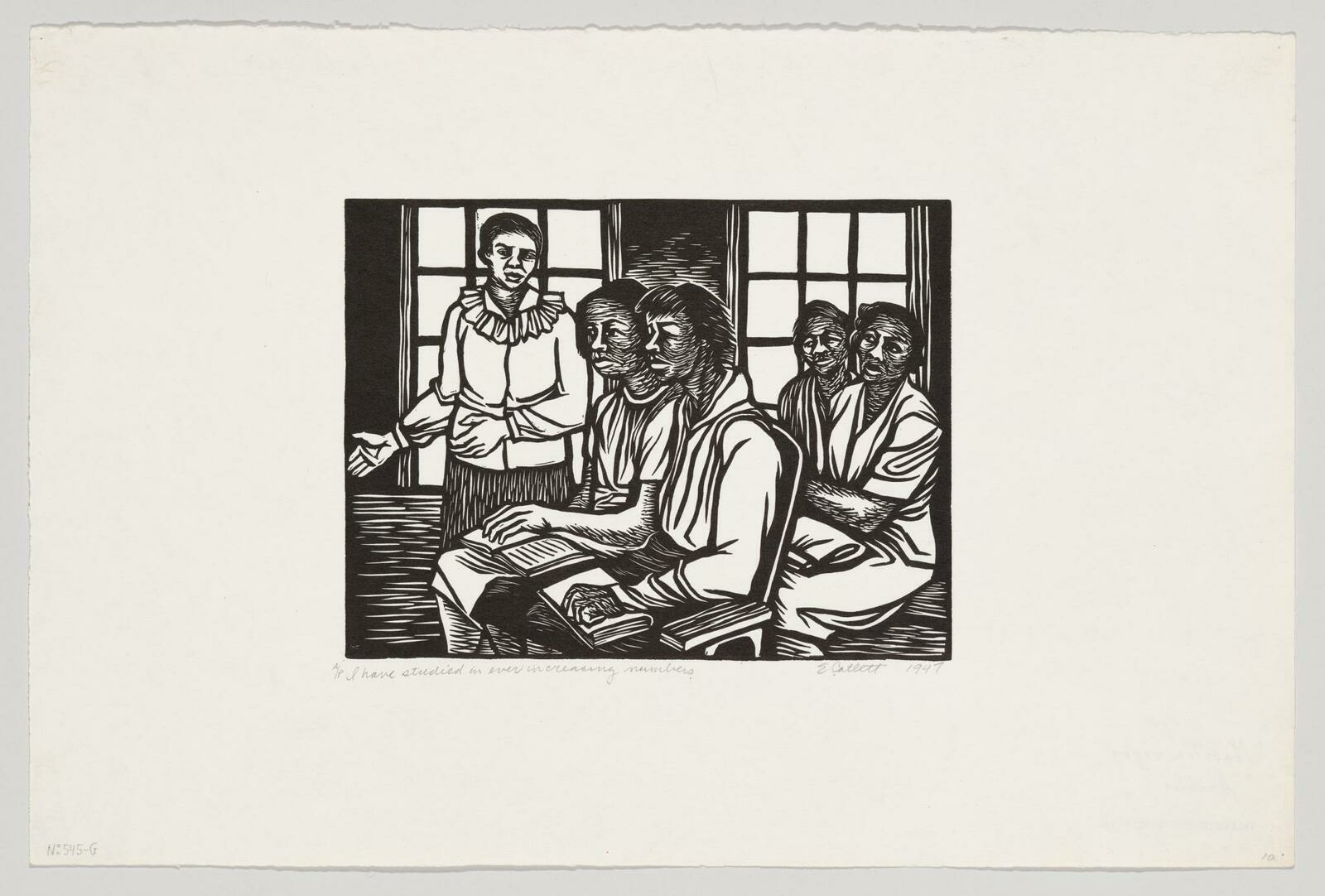 Four Black women sitting in a classroom with books on their laps while a standing woman lectures.