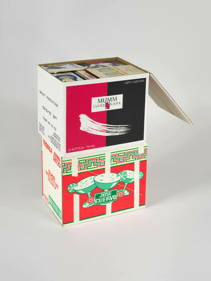 A black and red box of Mumm wine, filled with books, sits on top of a box of a brightly colored red and green Jose Cuervo box
