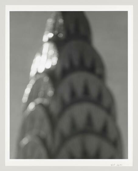 A fuzzy photo of the top of the Chrysler Building shimmering with sunlight.