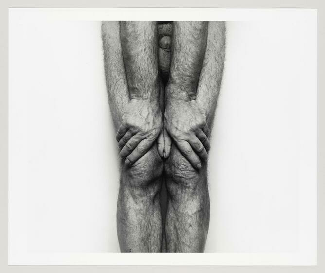 A man's hairy lower body with his hands strongly grasping his kneecaps