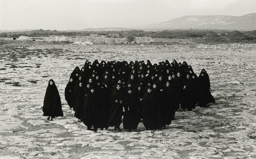 In a large desert, a group of veiled women are standing and staring at the viewer