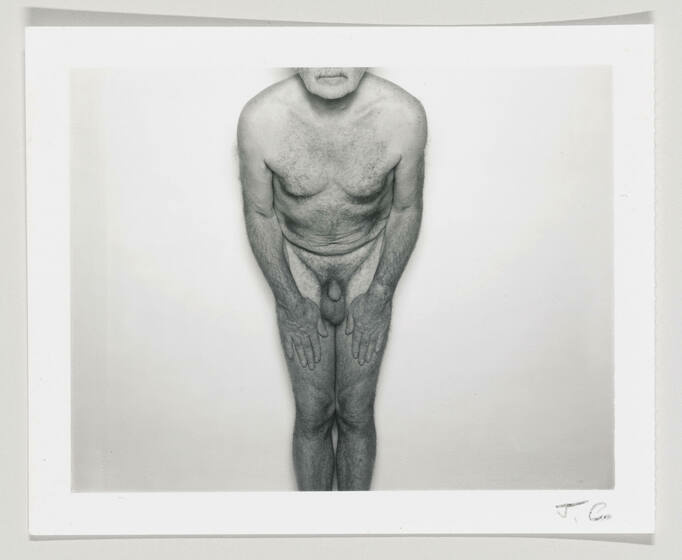 A black and white photo of a nude white man bending forward, with hands on his thighs.