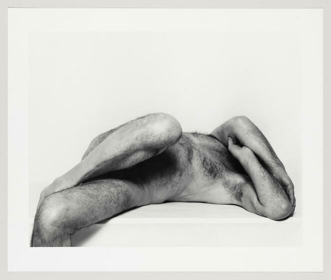 A hairy nude male reclining aganist a flat surface with crossed arms and legs