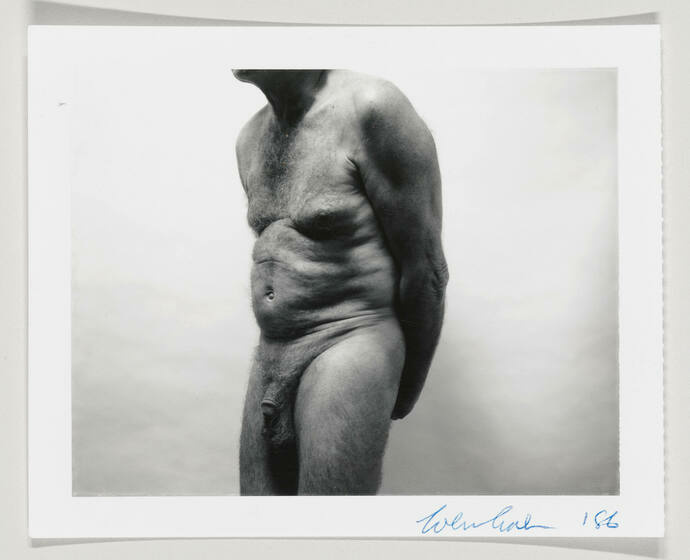 A man's nude body is shown slouching from just below the neck to right above the knee.