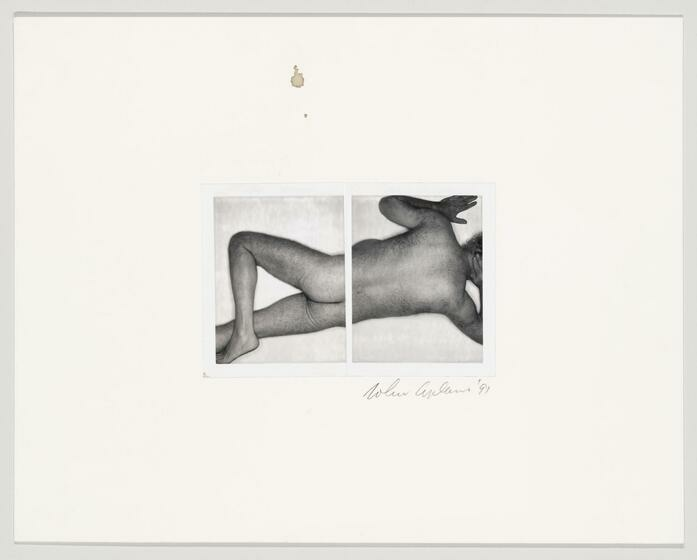 A nude body lays on stomach, legs crossed, arms at head.