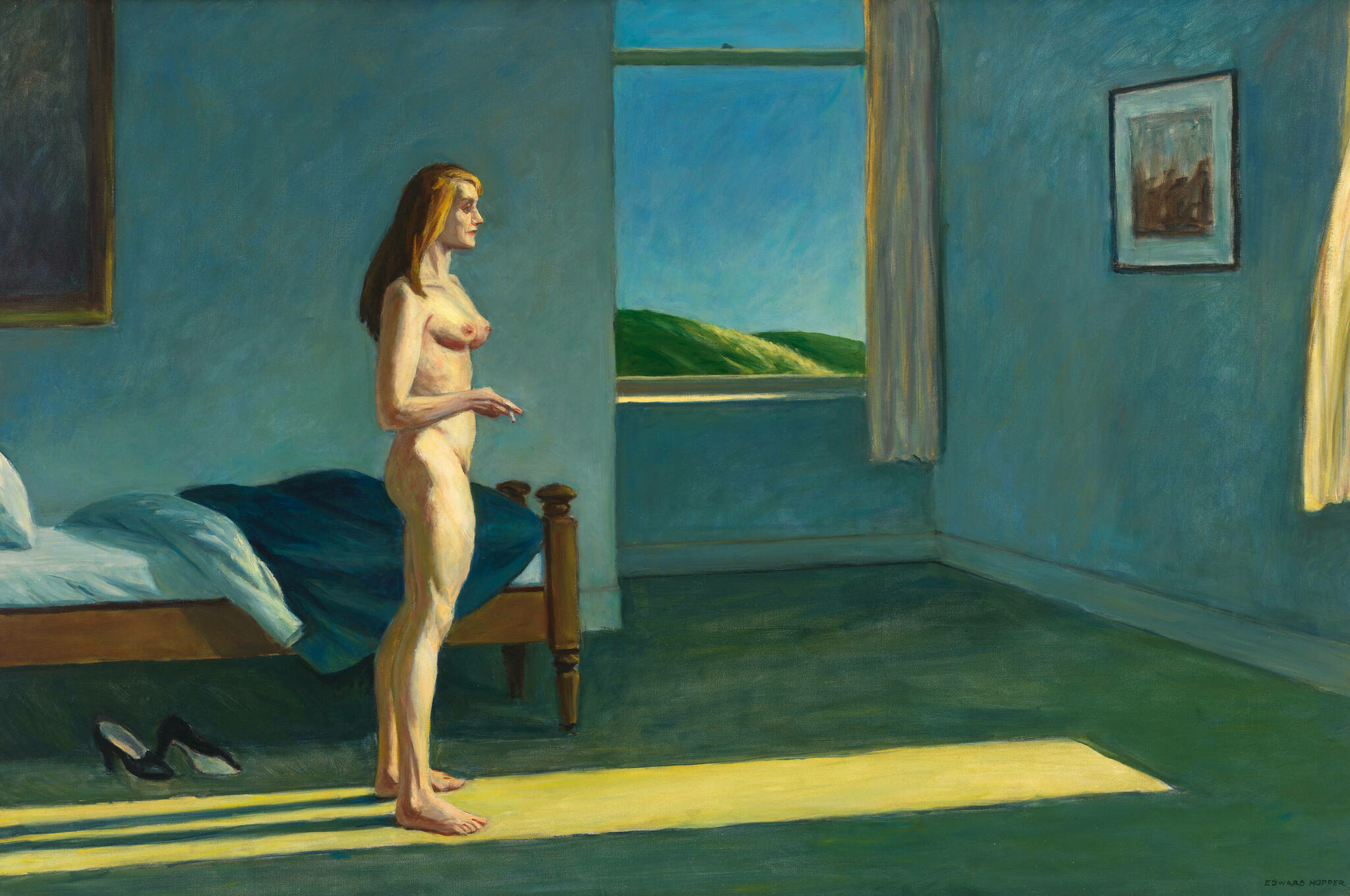 A nude white woman stands in a bluish bedroom and looks out a window as she holds a cigarette.