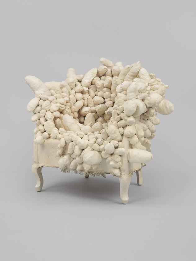An ivory armchair engulfed in soft globular shapes.