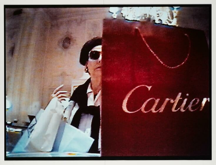 A garnet red Cartier bag sits in front of a white woman as her right arm carry's shopping bags