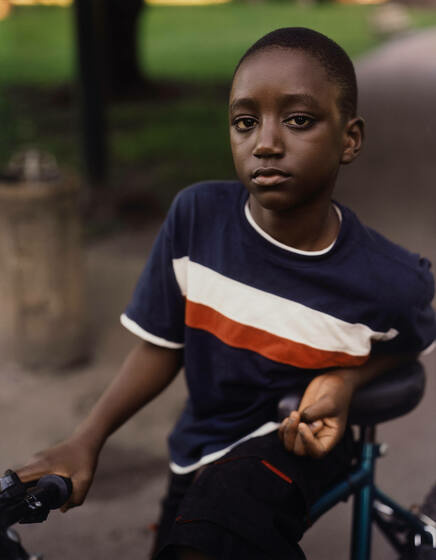 A young Black boy leans on a bike in the park and looks directly at the camera.
