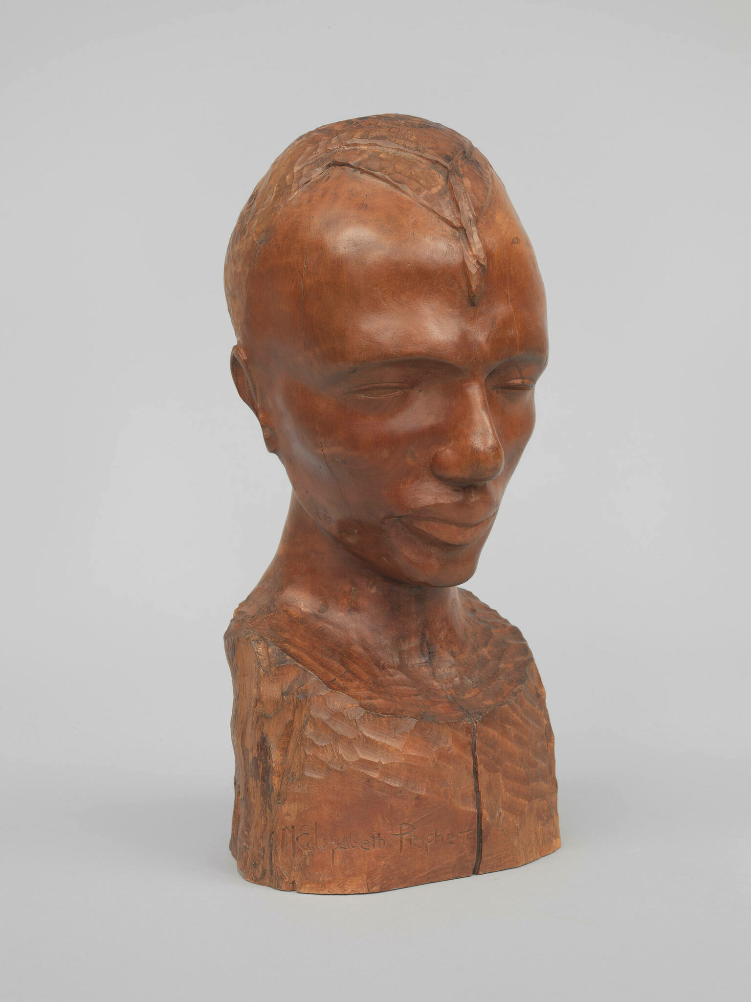 A cherry wood bust of a male head with closed eyes and upturned lips.