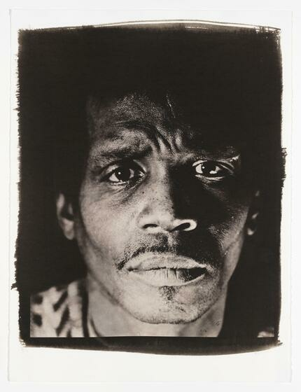 A brown monochrome portrait of a Black man with furrowed brows.