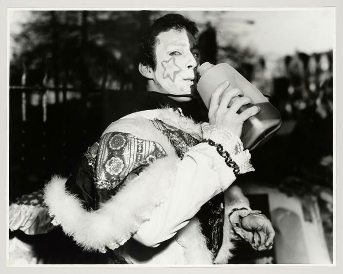 a white man in regalia grips a large bottle and stares at the camera