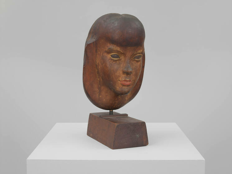 An aged wood sculpture of Alice Compton's head with remnants of paint, atop a wood base.