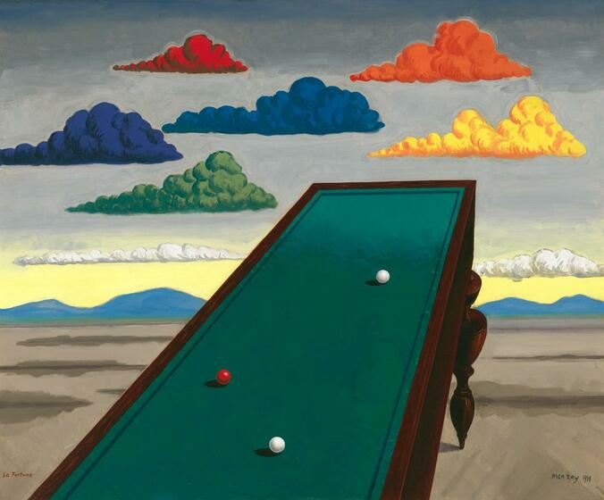 On a desert plain, a pool table with one red and two white pool balls extends toward a dull sky with yellow, blue, orange, and red clouds.