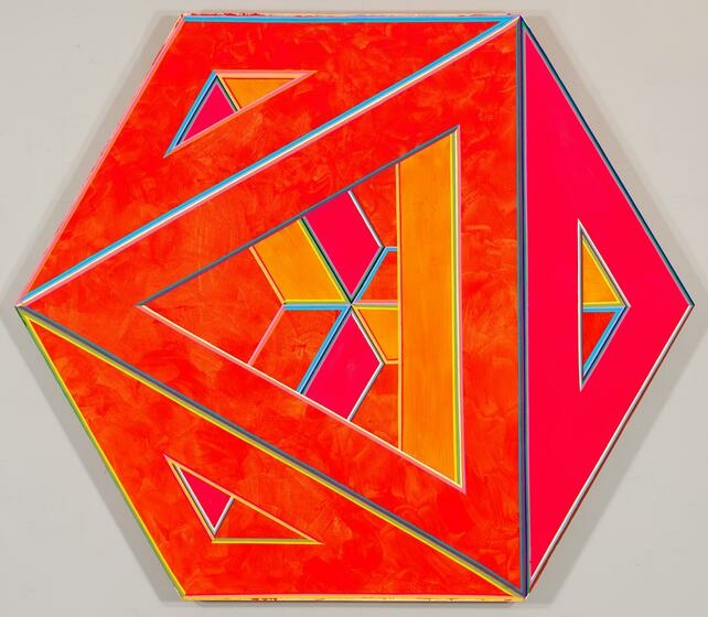 A three-dimensional hexagon in neon orange-reds, red-pinks, and orange-yellows and covered in triangular holes