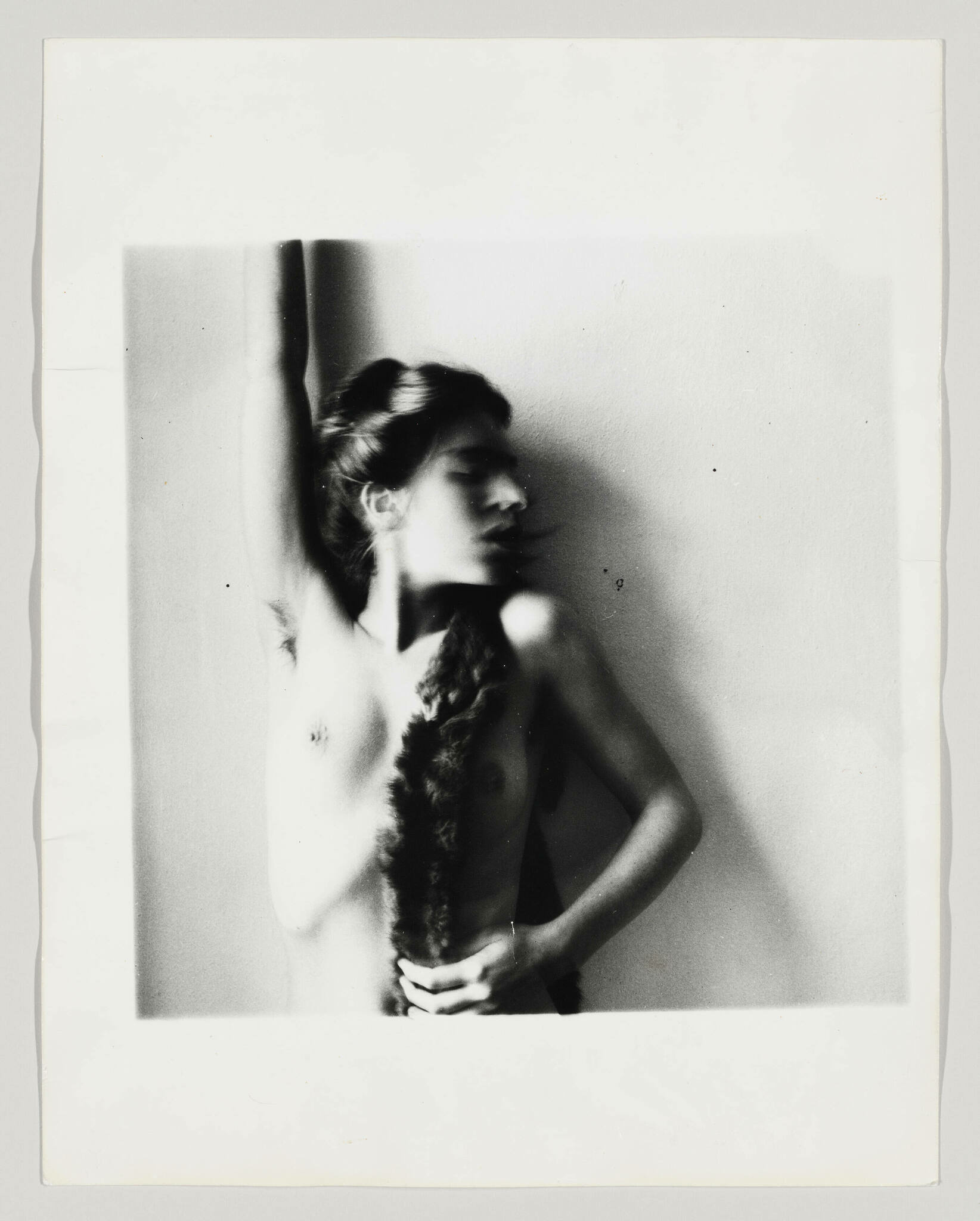 A nude woman looks to the right as her bent right arm touches her braid