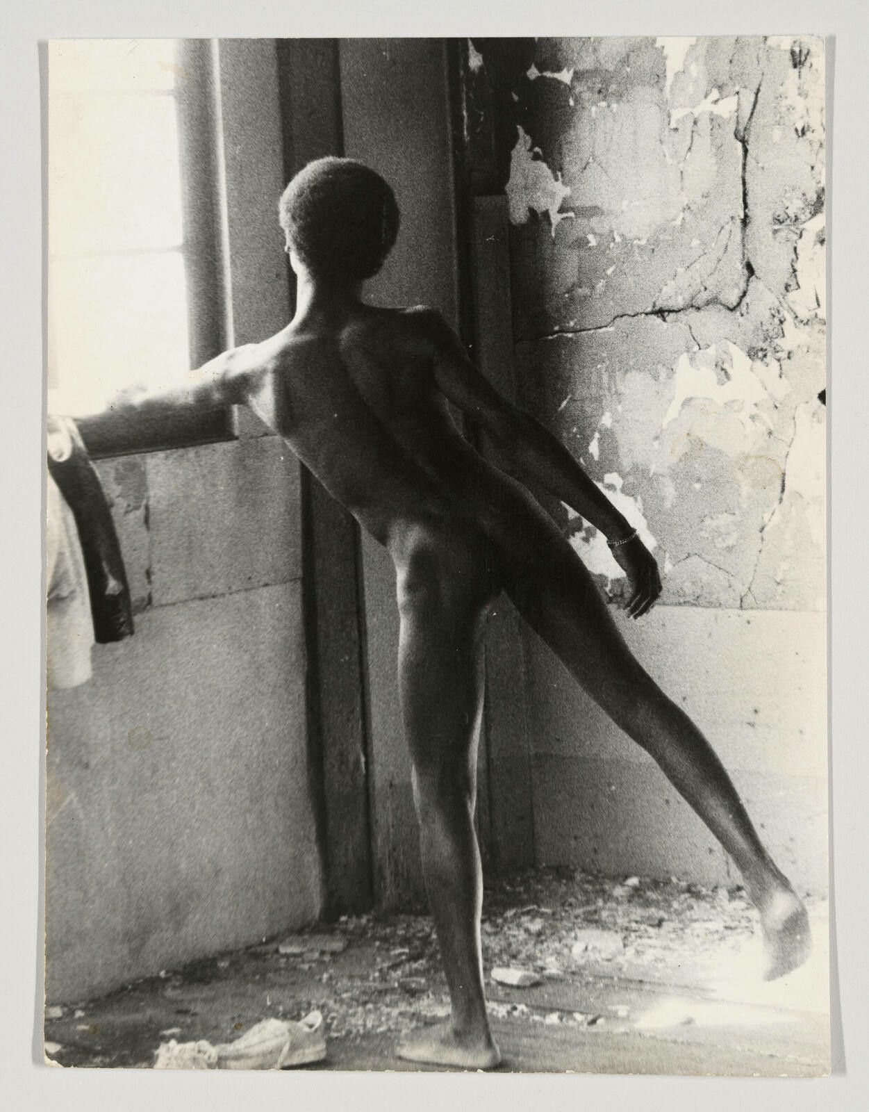 A naked Black man balances on one leg while looking out into the glistening light from a window in a dilapidated room