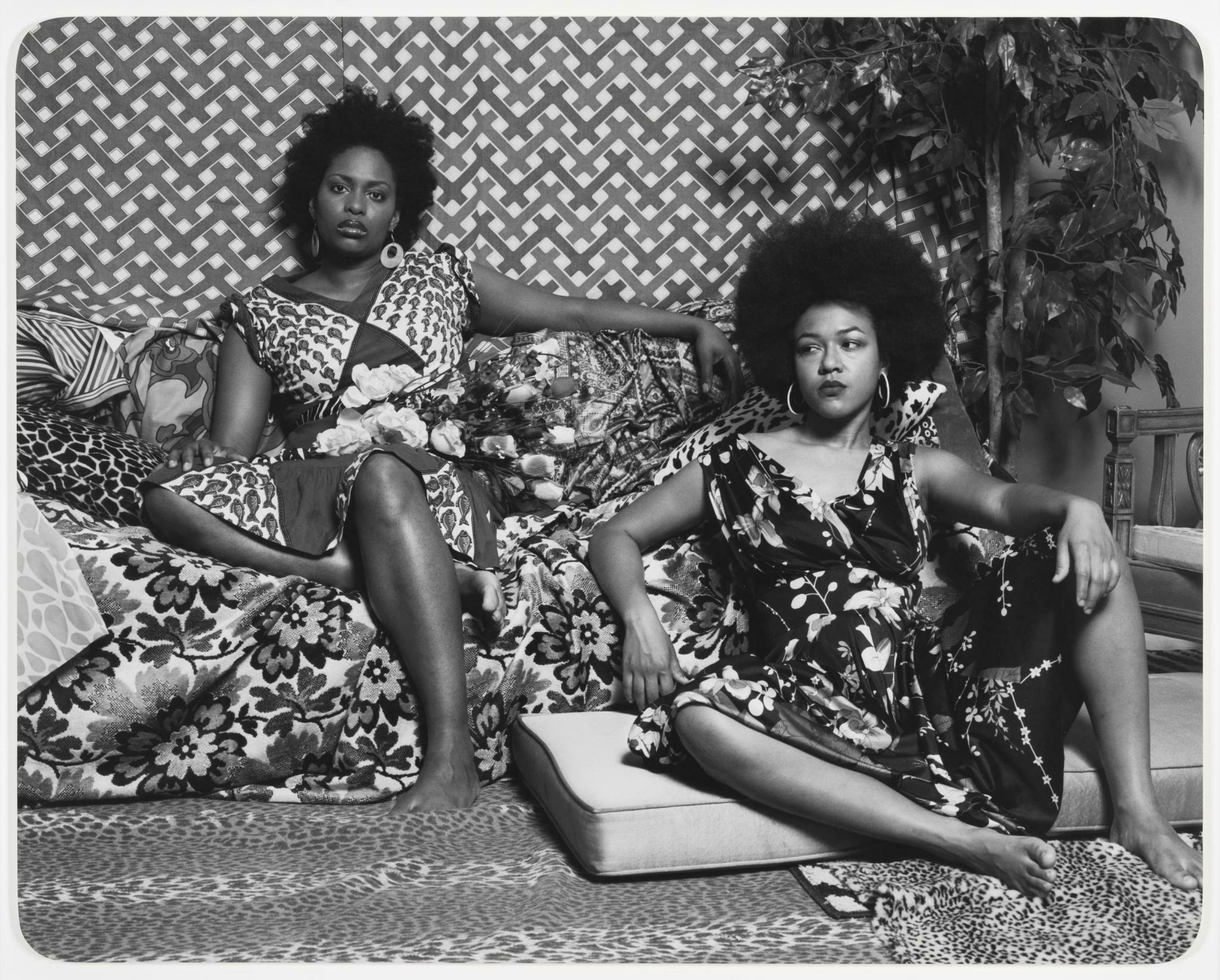 Two Black women wearing vibrantly patterned dresses sit in a similarly patterned interior.