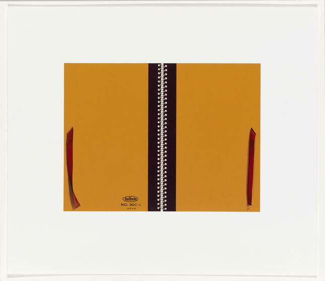 A yellow sketchbook with a dark brown binding and marron red ribbon is folded open