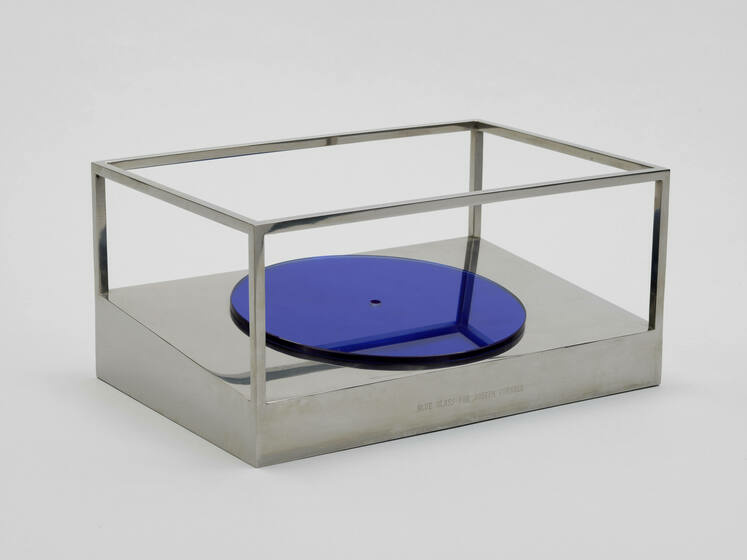 A reflective blue disk rests on the angled base of an open-sided steel cube
