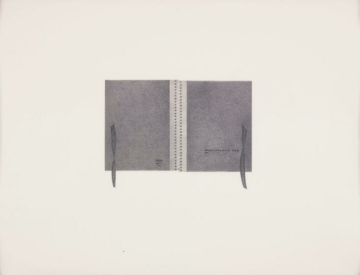 A grey sketchbook with a white binding and grey ribbon is folded open