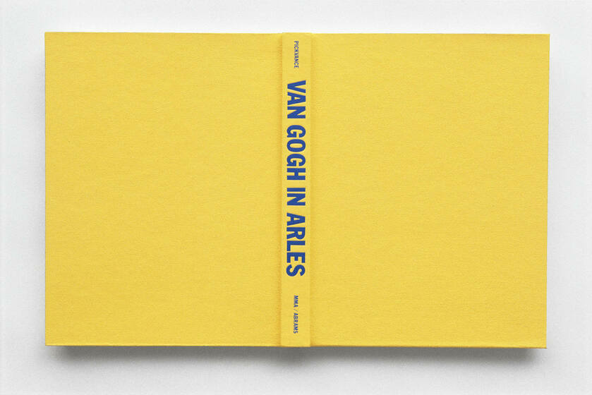 """A yellow book is spread opened and the binding reads """"Van Gogh in Arles"""""""