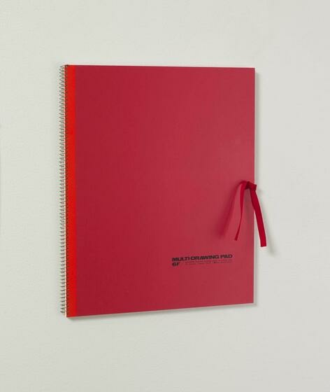 A marron sketchbook with bright red binding is closed with a red ribbon