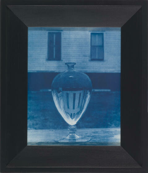 A cyanotype of a Venini vase on a sill with the farmhouse in the background inverted in the glass, framed by a black border.