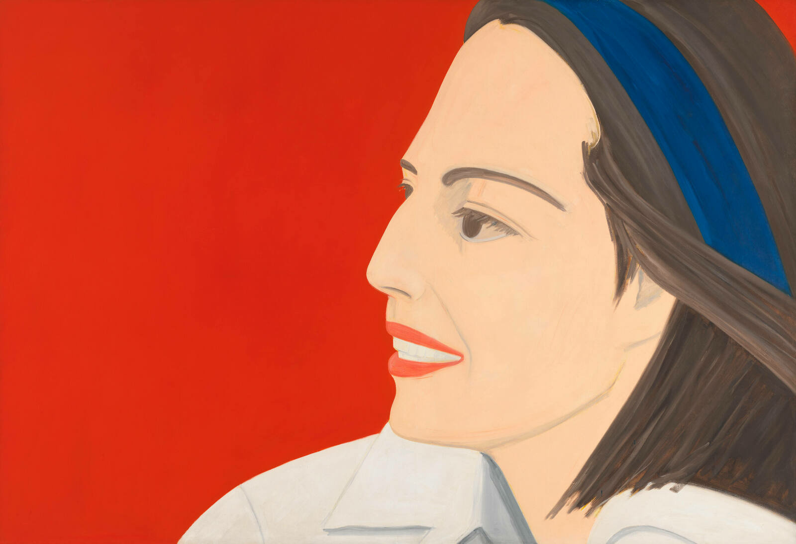 A woman wearing red lipstick smiles softly, her face in profile against a more vivid red background.