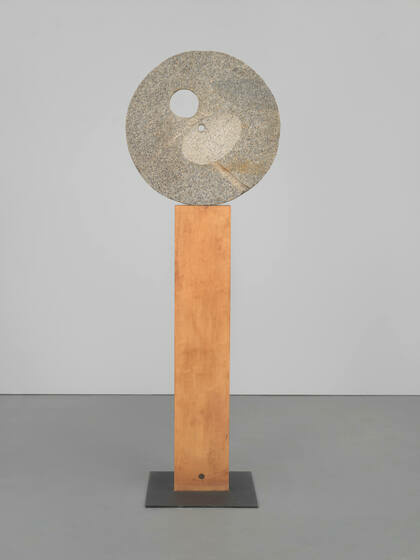 A flat circular grey stone with two smaller holes in it rests atop an upright wooden board.