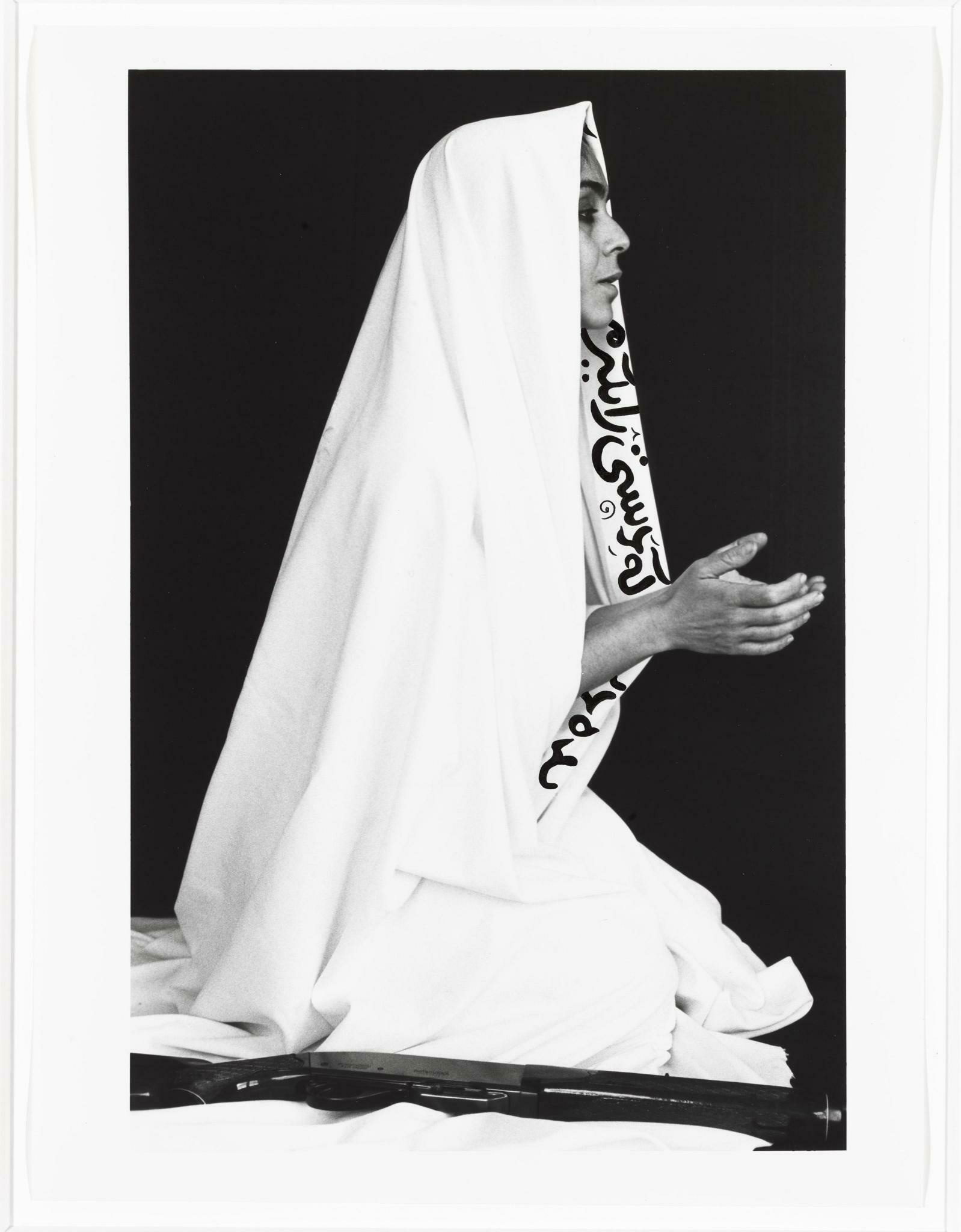 Seen from a profile view of a Iranian woman who is facing the right is wearing a white veil with Farsi text, has her hands in a prayer position, and has a gun near her bended knees
