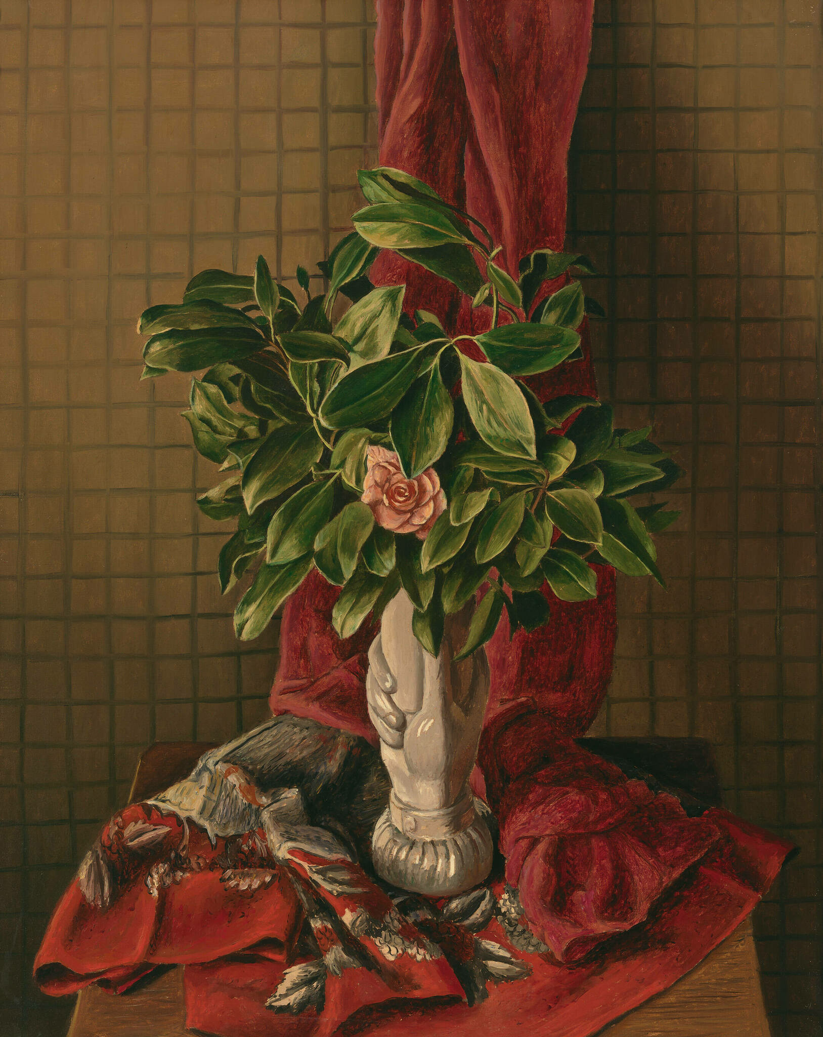 An ornate vase sits on draped red fabric, holding a full green plant with a single pink flower.