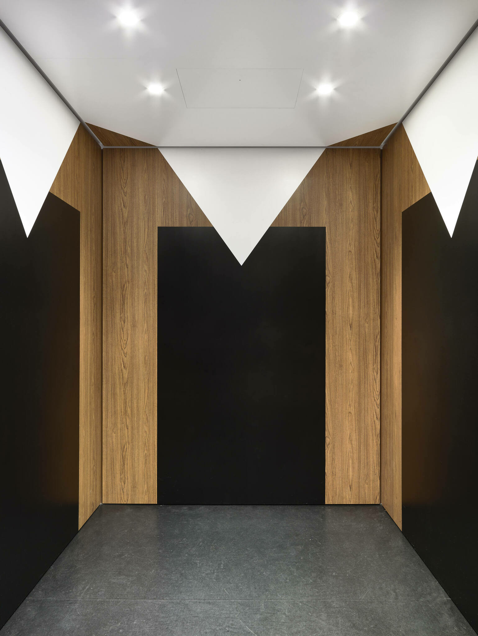 An elevator's interior with geometric wall designs resembling the underside of a table, wood-like columns in the corners for table legs and a white diamond predominating the ceiling for the table cloth
