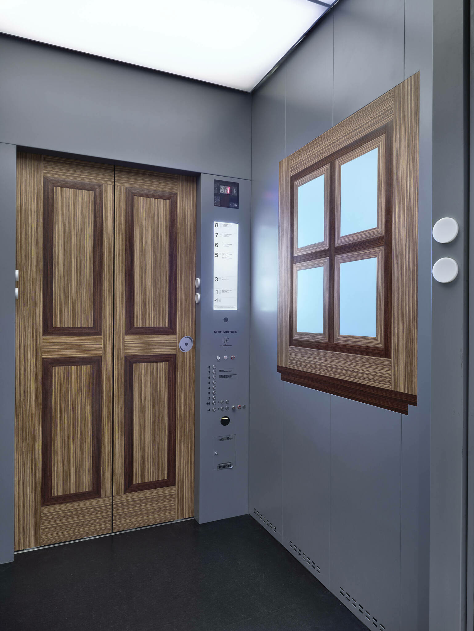 An elevator's gray interior with wall designs resembling wooden double doors and a wood-frame window