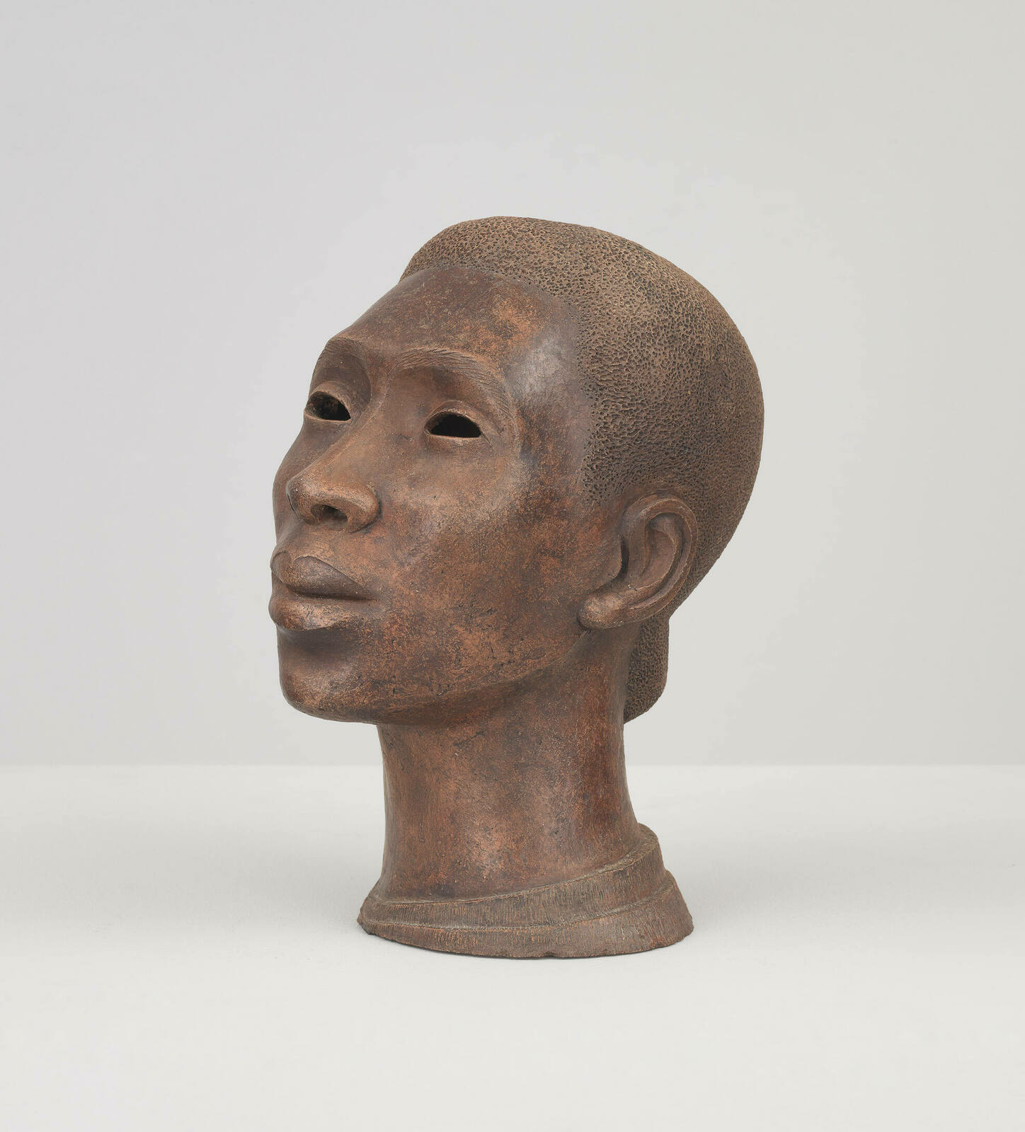 A portrait bust of a Black woman, her face lifted slightly towards the sky