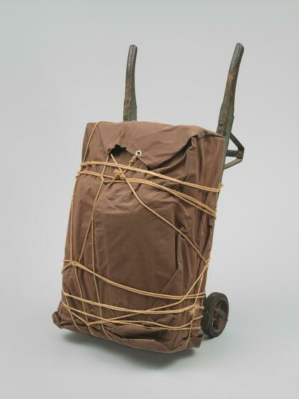 A lumpy, rectangular package wrapped in brown tarp and rope and supported by an aged, wooden hand truck.