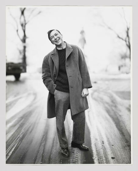 A short-haired white man in a peacoat, sweater, slacks, and oxfords stands on an unpopulated road with one hand in his pocket, his head titled as he smiles brightly.