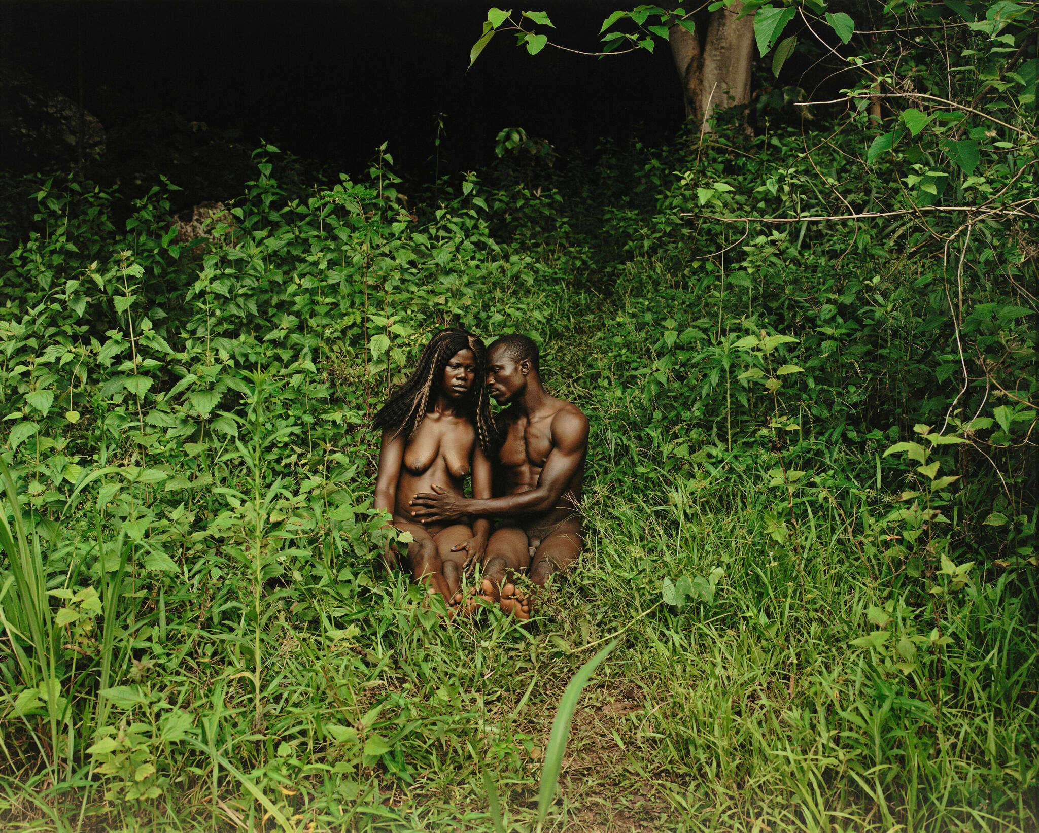 A Black couple sit in the nude in a lush green garden; the man's hand reaches across the woman's belly
