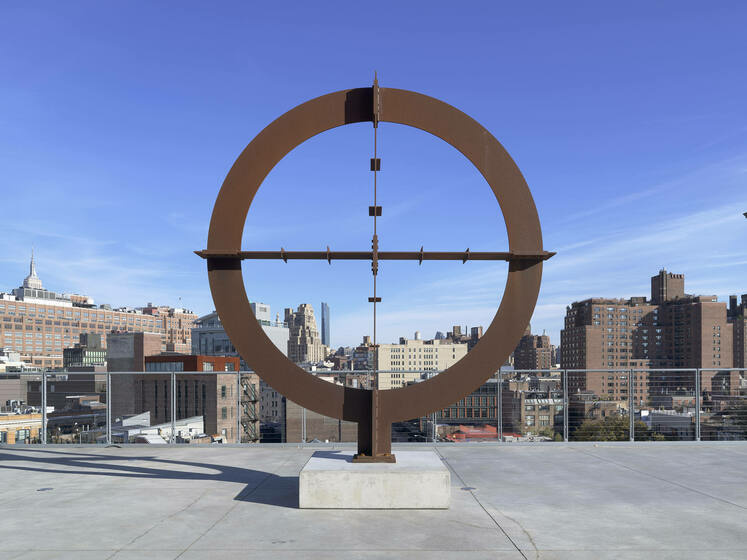 A giant reticle or encircled crosshair made of steel, installed on an open-air terrance backdropped by the cityscape.