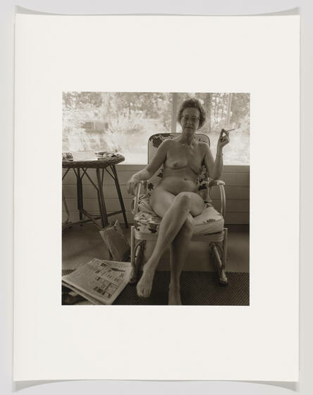 A fully nude middle-aged white woman holds a lit cigarette and sits on an armchair in a house