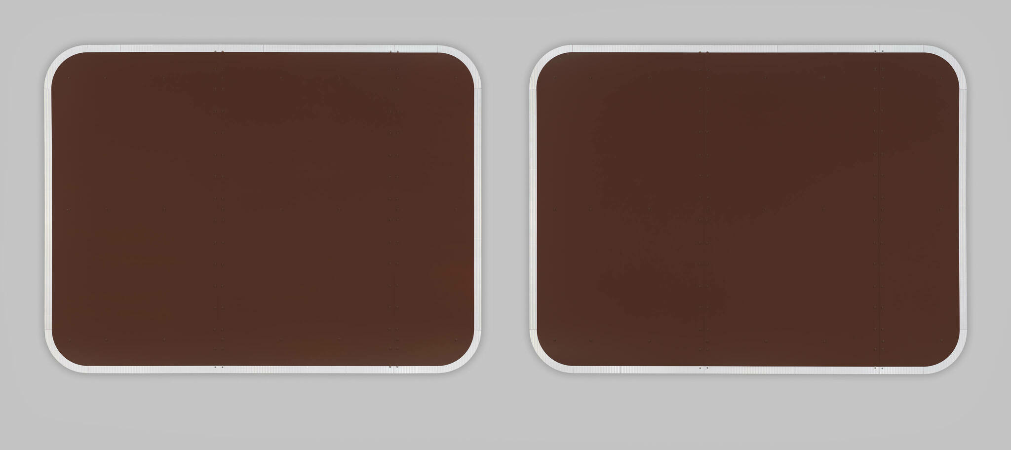 Two monochrome brown rectangular shapes like empty signs, with reflective tape around their edges