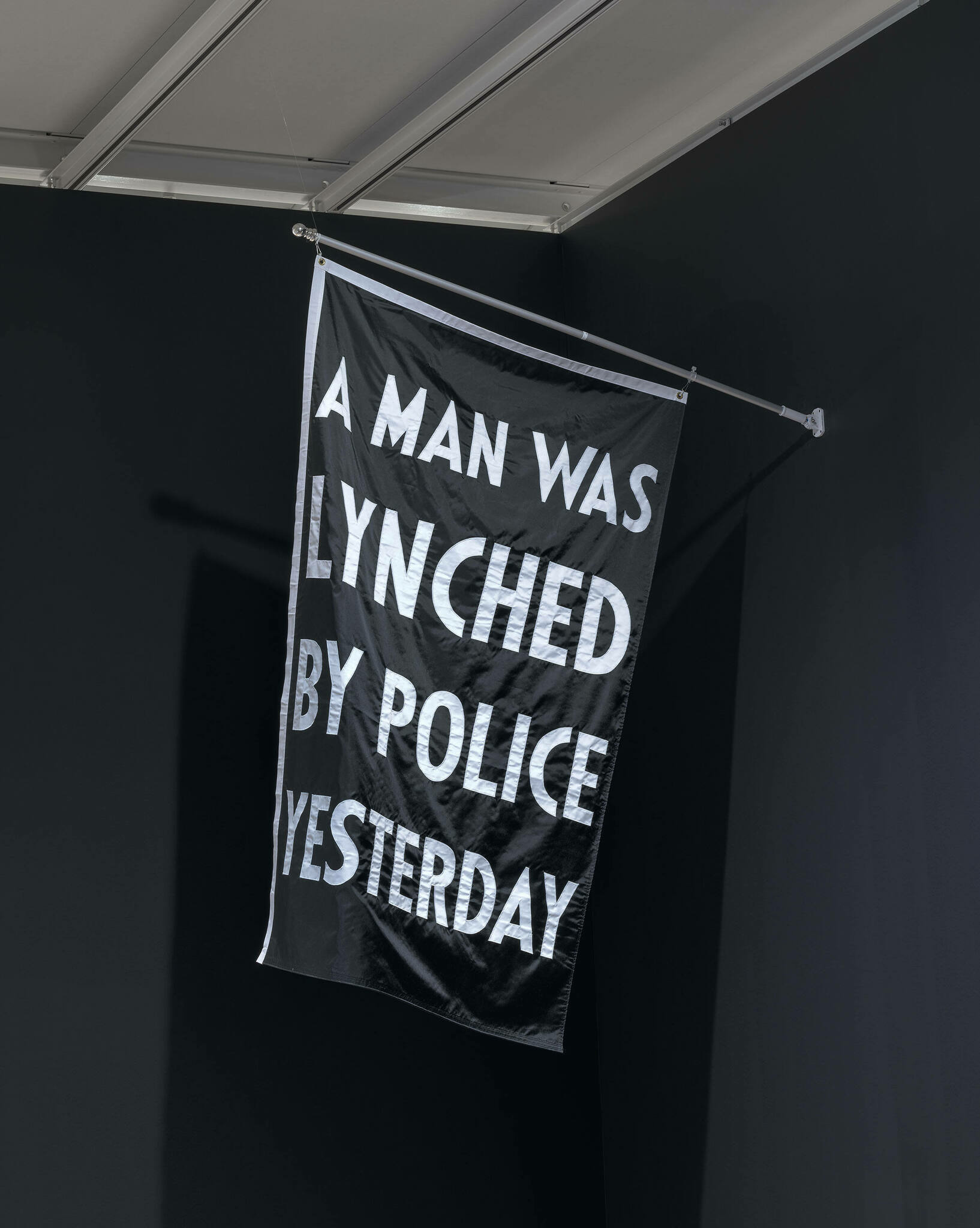 A black flag with white words reading A MAN WAS LYNCHED BY POLICE YESTERDAY.