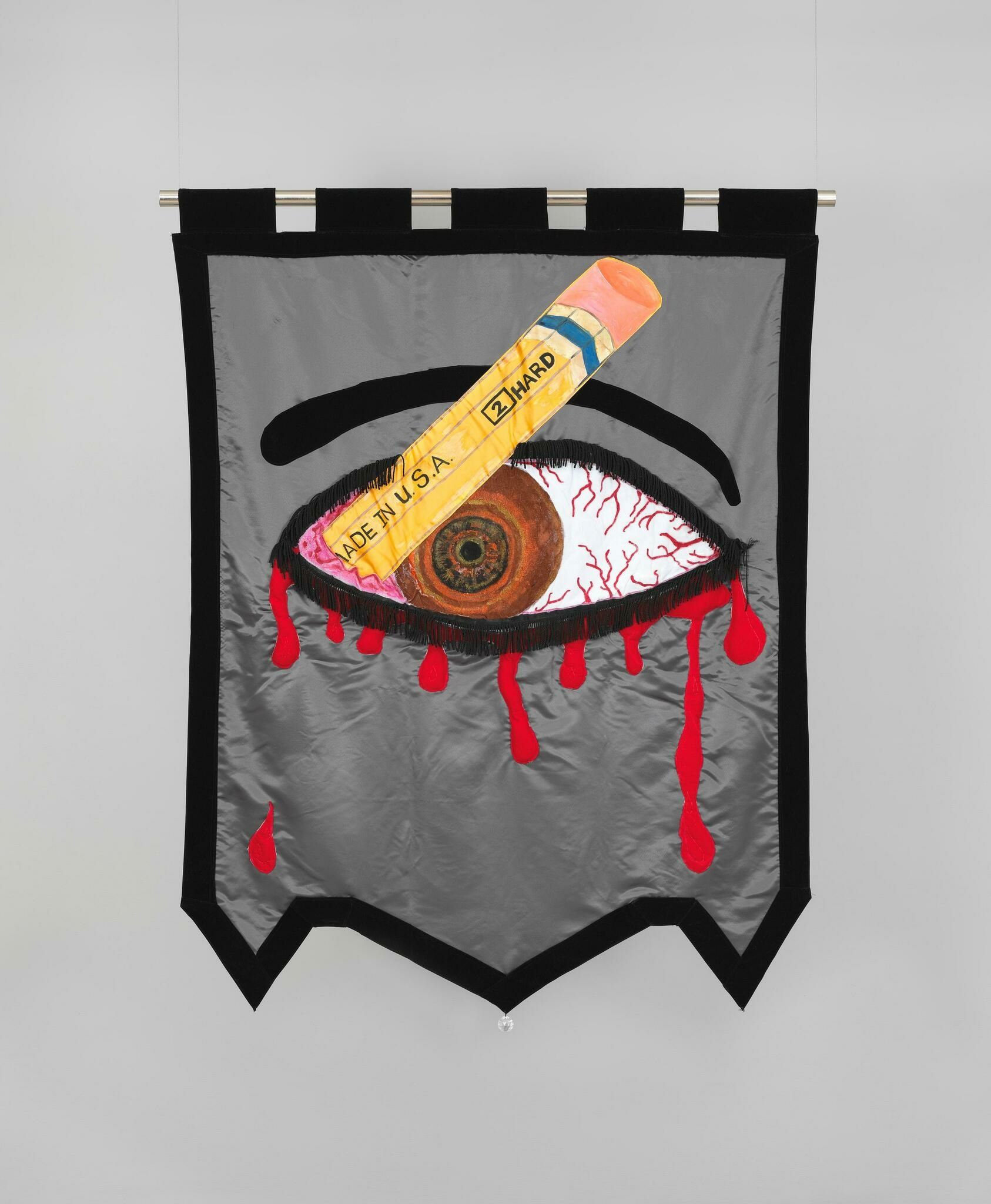 A sewn banner with a bloody brown eye stabbed by a number two pencil against a grey background.