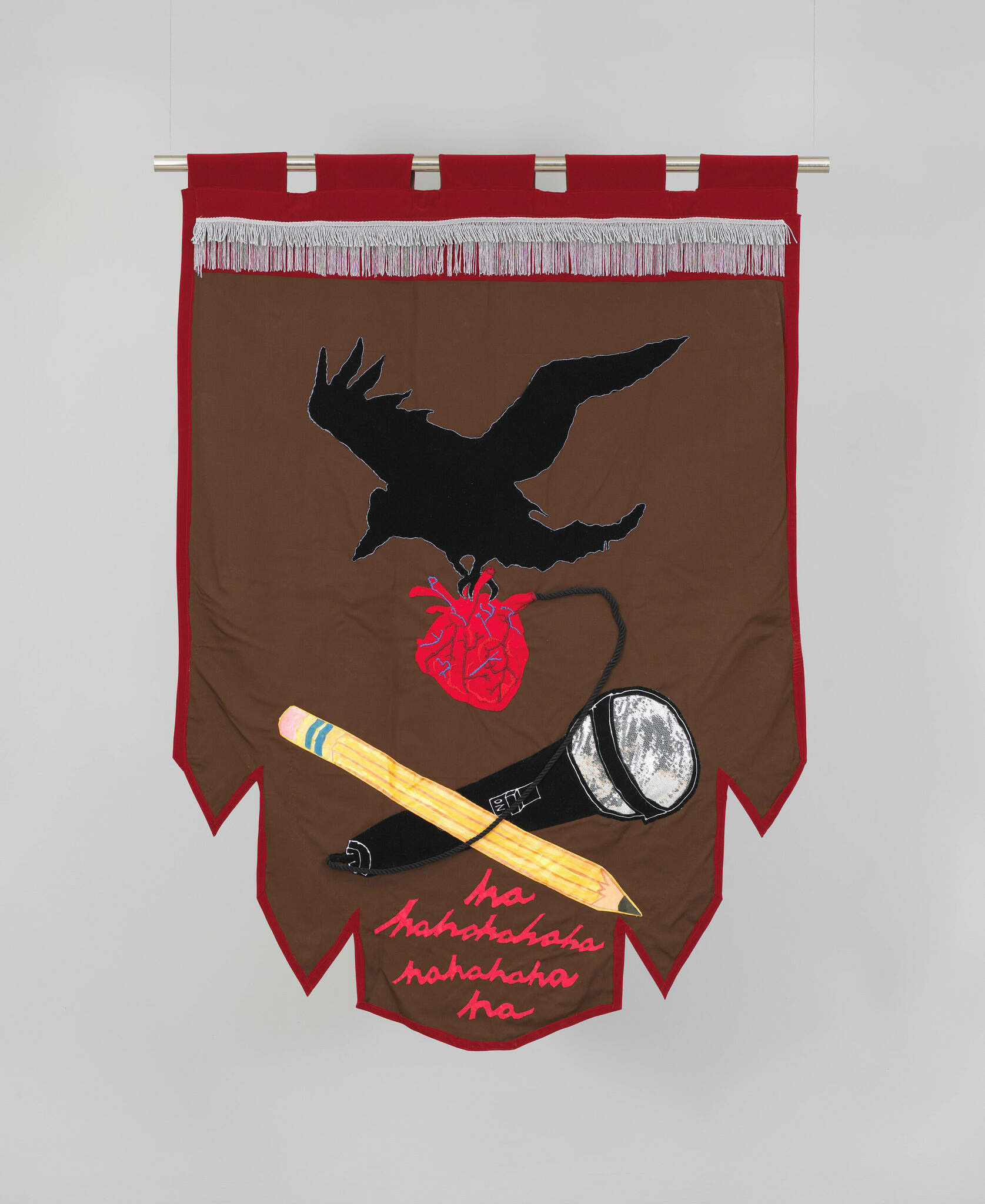 """Fabric banner with black bird grasping anatomical heart above pencil and microphone. Text in cursive reads """"hahaha."""""""