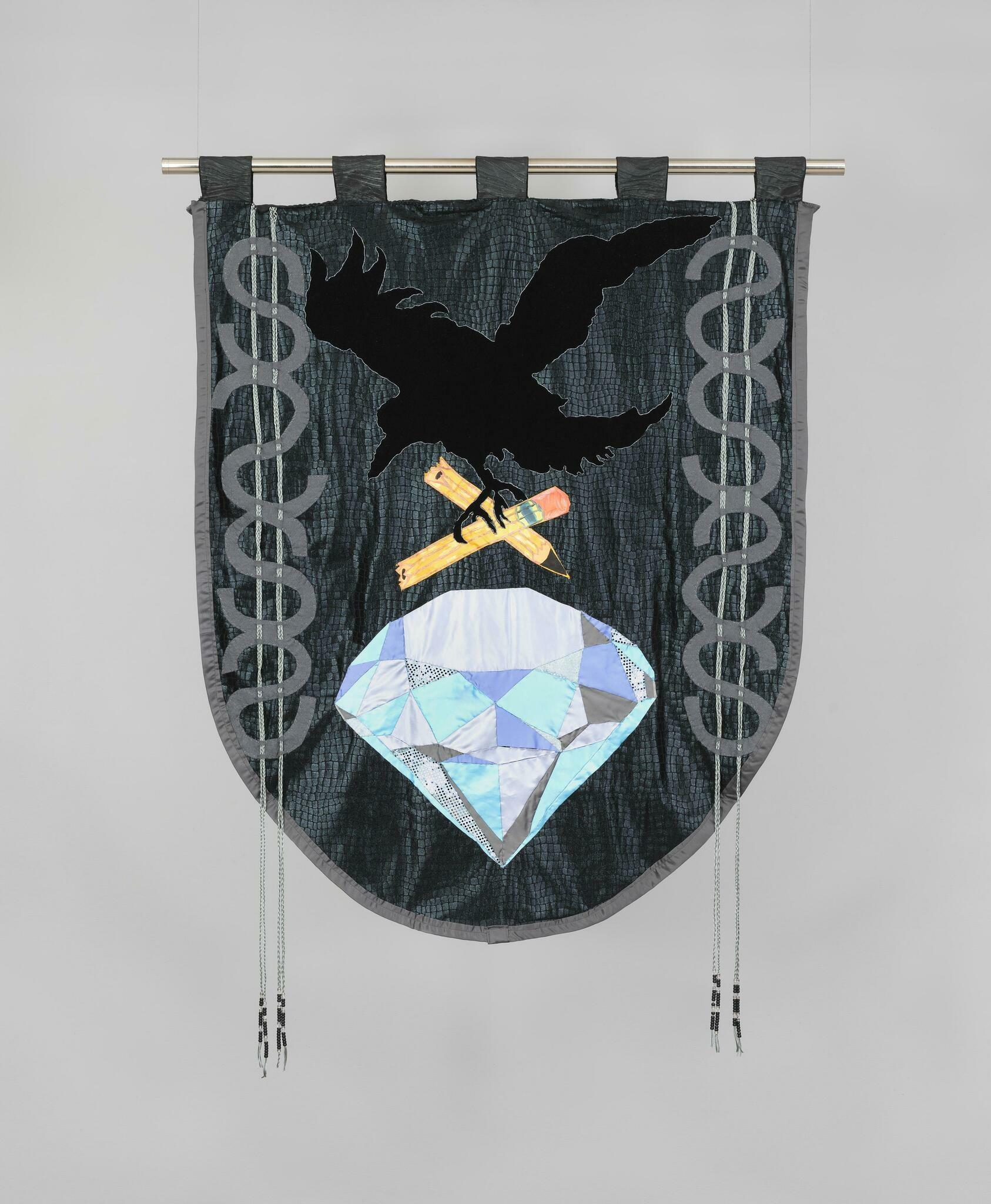A black bird grasps two halves of a broken yellow pencil above a large diamond on a dark grey quilted banner.