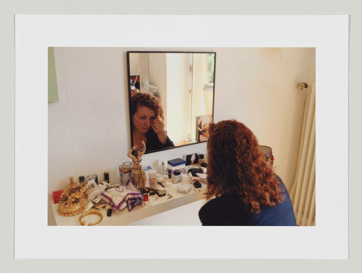 A curly, red-headed woman sits at a messy vanity doing her make-up