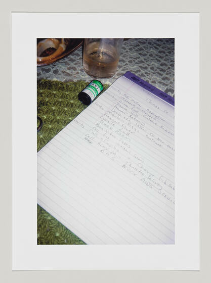 A notepad with a to-do list sitting on a lace-covered table with a roll of film and class next to it.