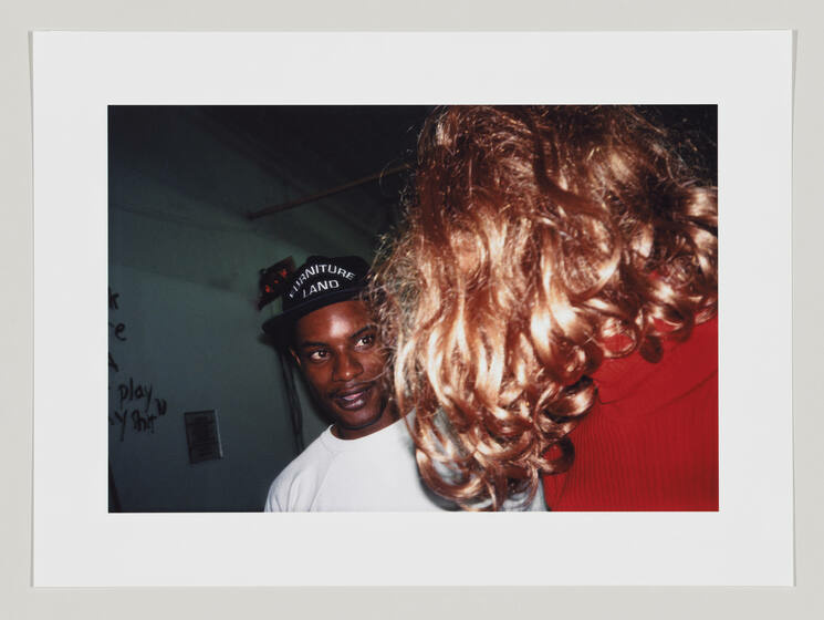 A dynamic shot with a Black man looking at a blond, curly-haired woman.